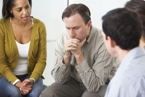 photo of a pensive man in a support group meeting